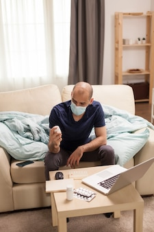 Male patient looking at pills bottle in time of a video call with doctor during global pandemic.