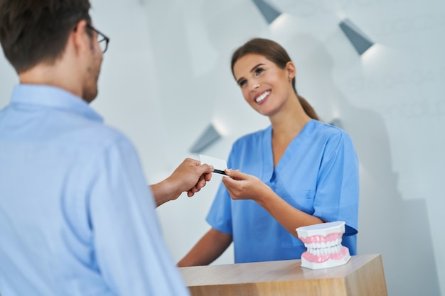Male patient paying for dental visit in clinic