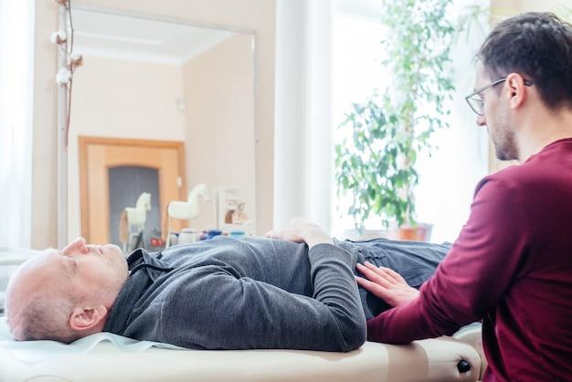 Cst 정골 클리닉, 정골 요법 및 수동 요법의 마사지 테이블에 누워 두개골 천골 요법을 받는 남성 환자