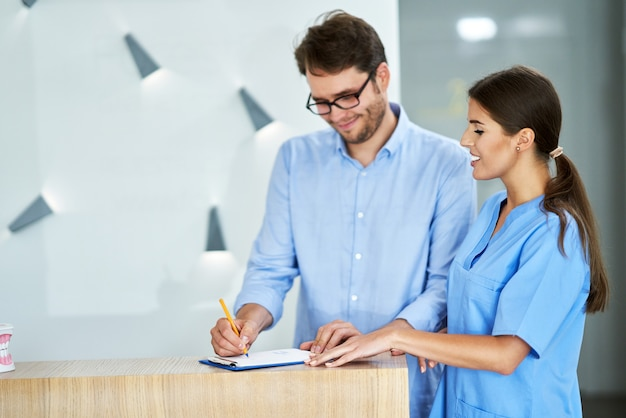 Male patient signing documents in dental clinic