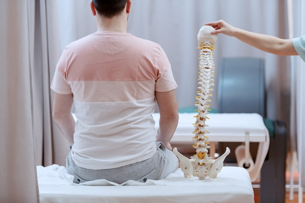 Male patient sitting on the hospital bed with backs turned. next to him is nurse holding spine model.