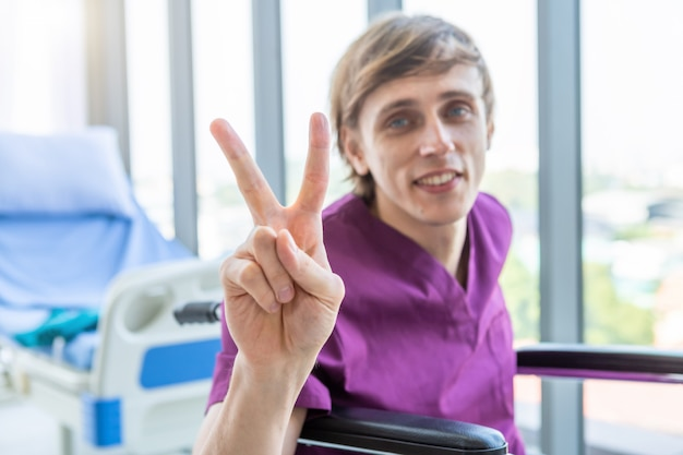 Male patient sitting in a wheelchair showing peace sign