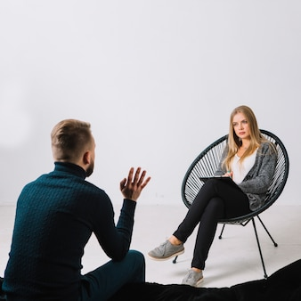 Male patient talking with female psychologist during the therapy against white wall