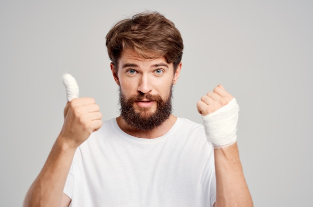 Male patient in a white tshirt with a bandaged hand posing isolated background