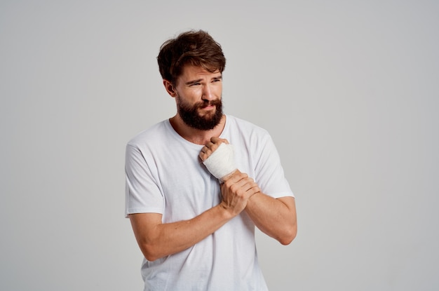 Male patient in a white tshirt with a bandaged hand posing light background