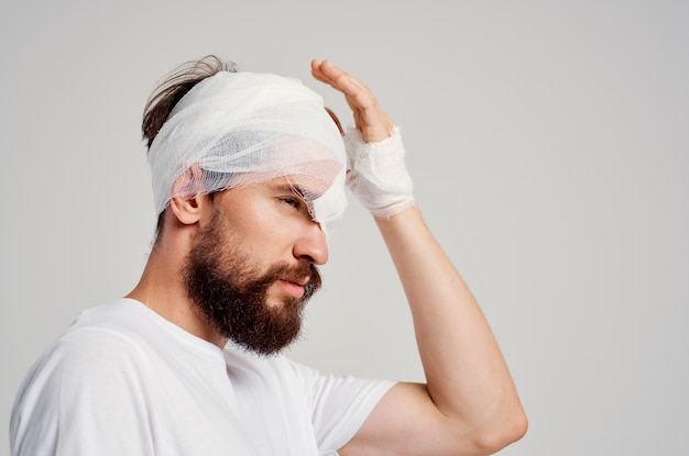 Male patient with bandaged head and eye hospitalization light background