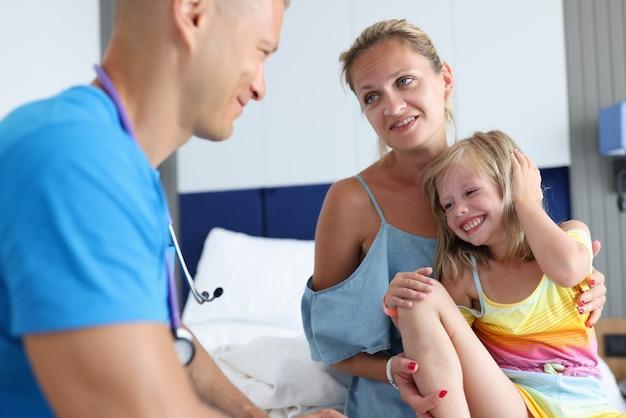 男性の小児科医は、医療の予約時に小さな女の子と母親と通信します