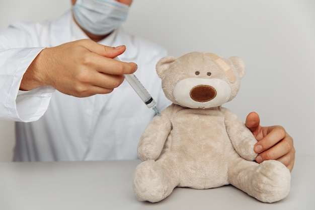 Male pediatrician makes an injection for sick teddy bear