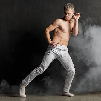 Male performer posing in jeans with socks and smoke