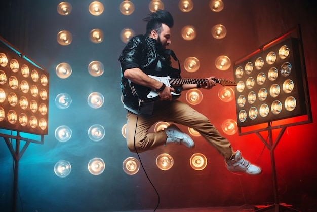 Male performer with electro guitar in a jump on the stage with the decorations of lights.