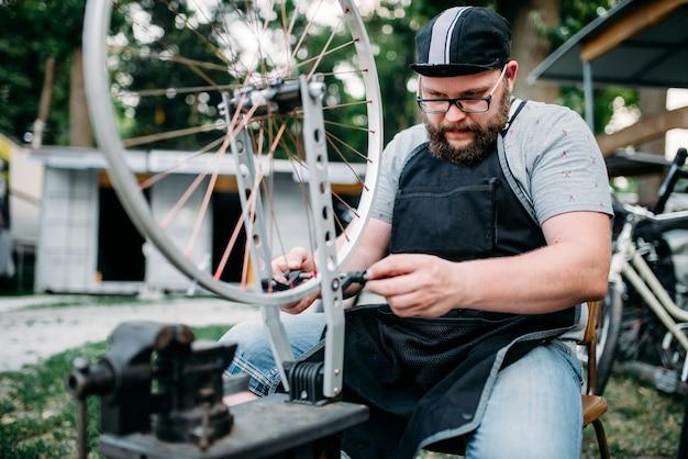 男性が自転車のスポークとホイールを調整する
