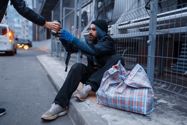 男性の人は、街の通りでひげを生やした汚いホームレスにホットコーヒーのカップを与えます。