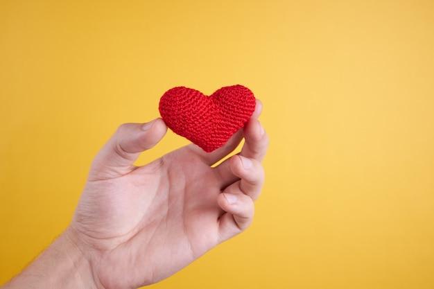 남성 사람은 노란색에 그의 손에 마음을 잡으십시오. 로맨스와 발렌타인 데이 개념.