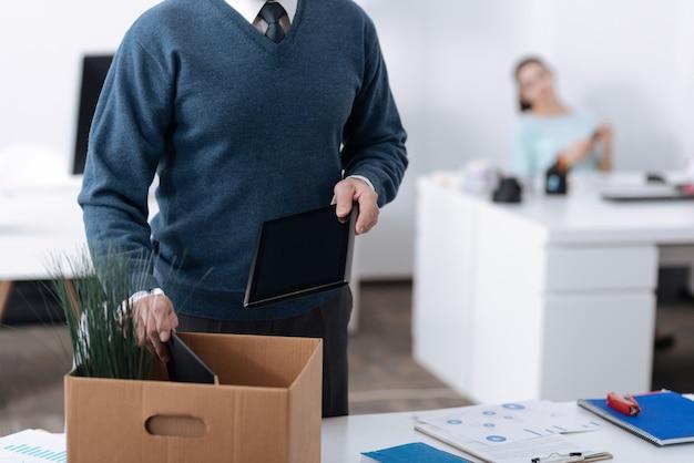 ノートブックを箱に入れながら職場の近くに立って左手にタブレットを持っている男性