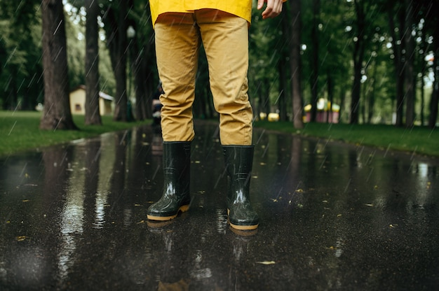 レインケープとゴム長靴の男性、路地の雨天。男は雨の日にサマーパークでポーズをとる。水の保護、滴