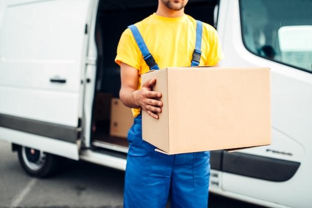 Мужчина в форме держит в руках картонную коробку, распределительный бизнес. доставка груза. пустой прозрачный контейнер