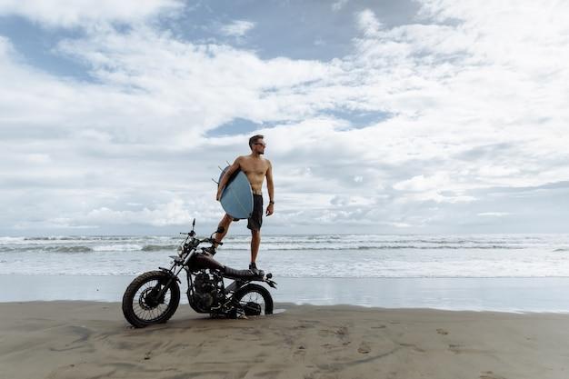 スポーツバイクに立っているときにインスピレーションを探している男性。サーフボードを手に持っています。海の近くでレクリエーションを楽しんでいる若い男のサーファー。