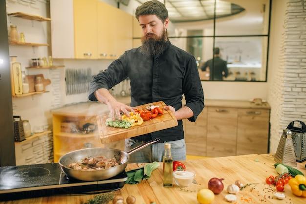 Мужчина кладет овощи в сковороду с жареным мясом на кухне.