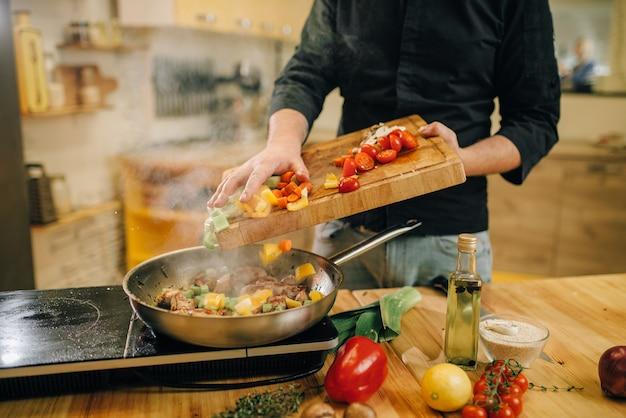 Мужчина кладет овощи в сковороду с мясом