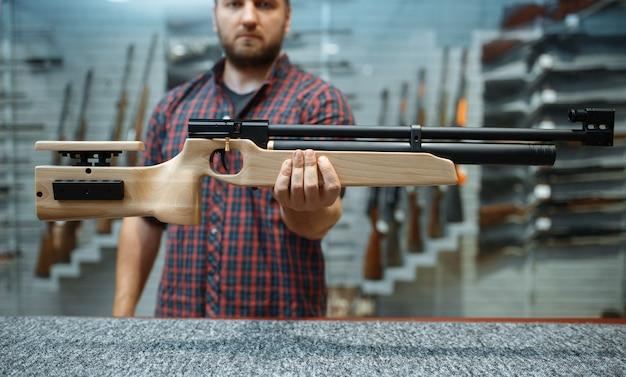 男性は銃専門店のショーケースで空気圧ライフルを見せます。武器店、狩猟、スポーツ射撃の趣味のスタンドにハンターのための機器