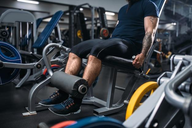 男性の人がジムでエクササイズマシンで足を訓練します。