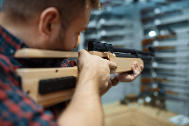 銃専門店で空気圧ライフルを持つ男性