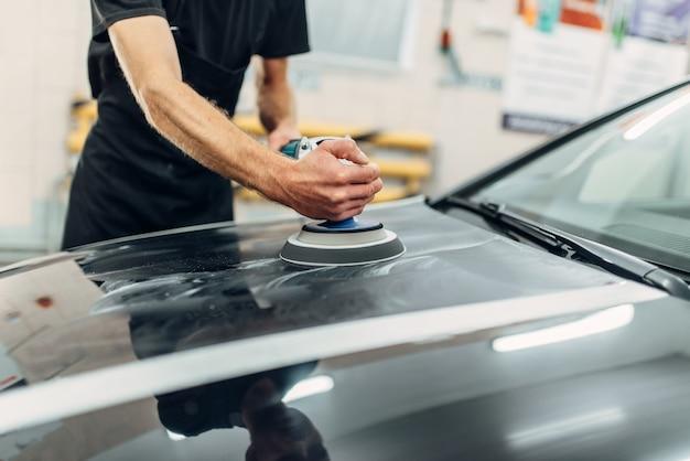 Мужчина с полировальной машинкой чистит капот автомобиля.