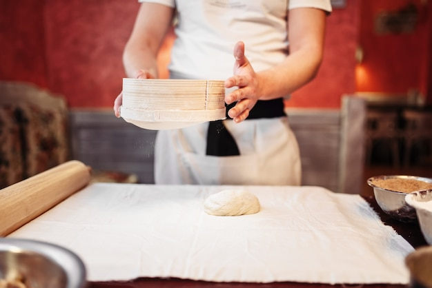 男性の人は、木製のキッチンテーブルの上の生地で動作します。自家製シュトルーデル料理