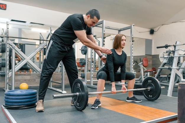 운동을 할 젊은 여성을 돕는 남성 개인 피트니스 트레이너
