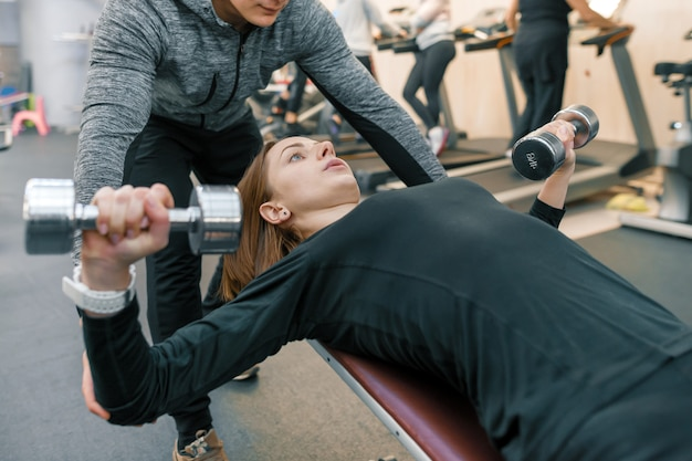Male personal fitness trainer helping young woman