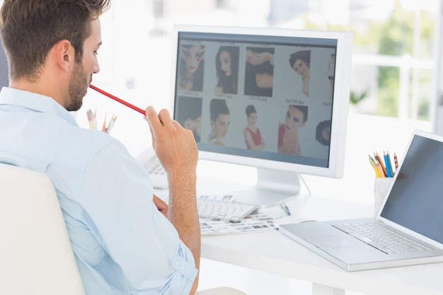 Male photo editor working on computer in office