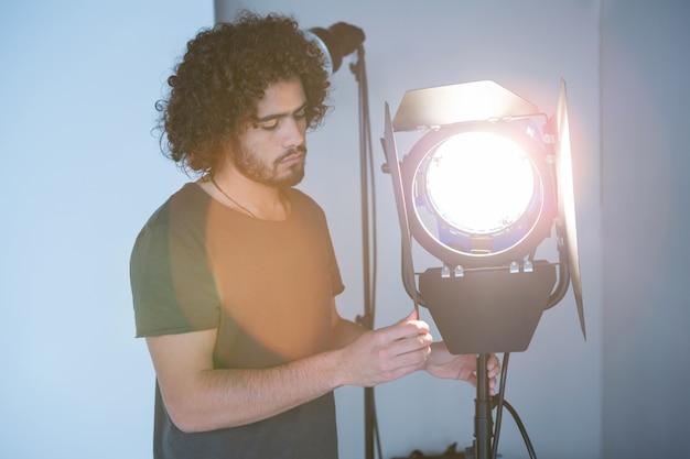 Мужской фотограф регулирует прожектор