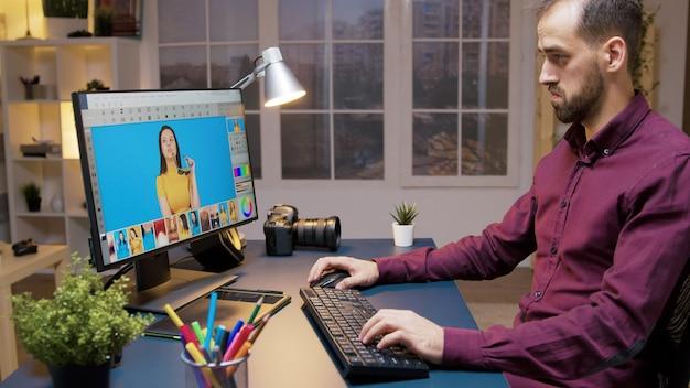 남성 사진 작가는 창의적인 사무실에서 사진을 편집합니다. 리터칭용 소프트웨어.