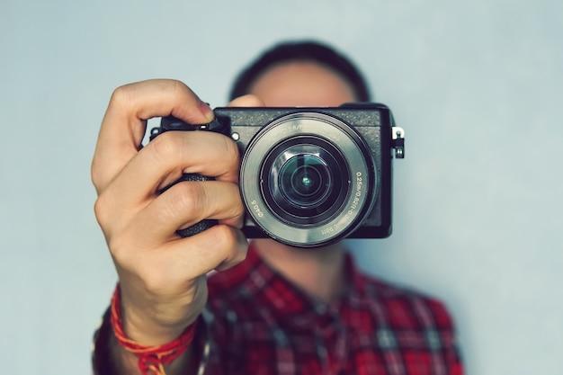 Фотограф-мужчина держит камеру в руках. беззеркальная камера крупным планом в руке молодого человека на синем фоне. репортер делает снимок. фотограф смотрит в камеру.