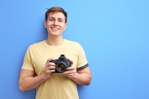 プロのカメラを手に持ってカメラに微笑んでいる男性写真家が写真を撮ります。青い背景の上に分離されたカジュアルなtシャツの笑顔の男