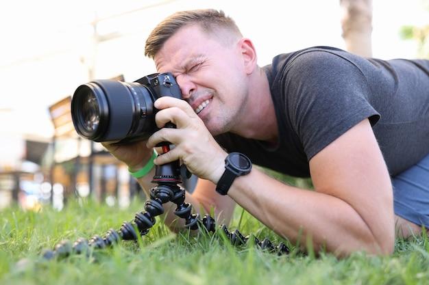 Фотограф-мужчина делает фотографии на штативе, лежа на земле, обучение профессии фотографа