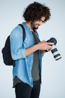 Фотограф мужского пола, рассматривающий захваченные фотографии в ее цифровой камере