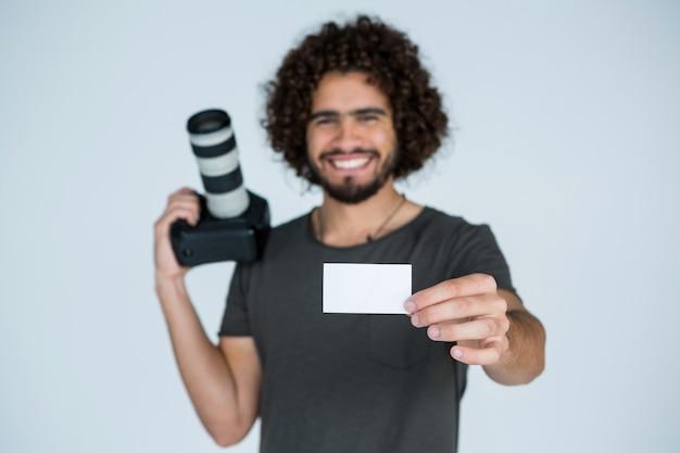 Мужской фотограф показывая визитную карточку в студии