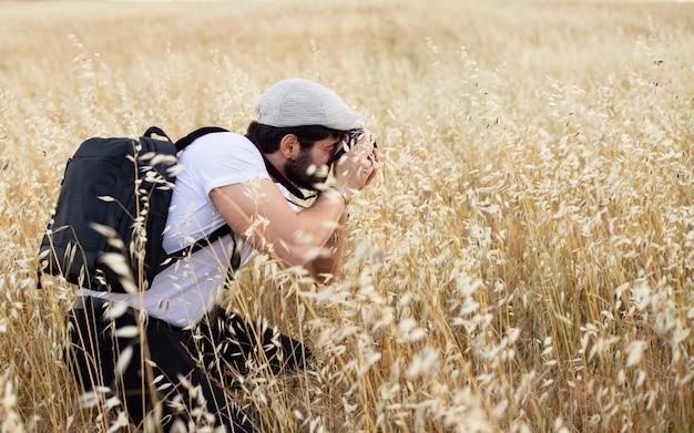 男性写真家が大麦で写真を撮る