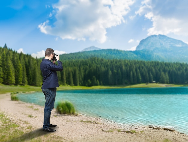 Male photographer taking picture of lake on digital camera, green wood and mountains