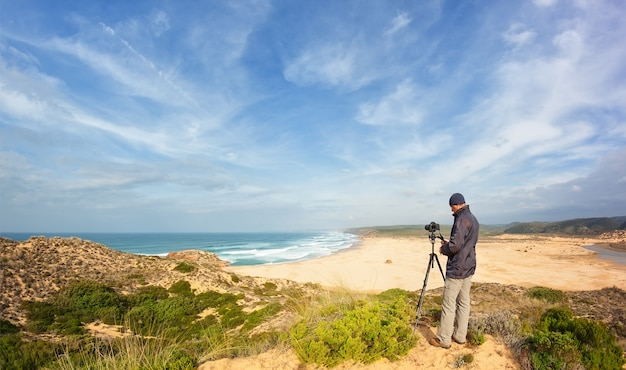 Male photographer traveling and photography in the dunes. with tripod and camera.