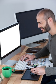 Male photographer using graphic tablet at desk