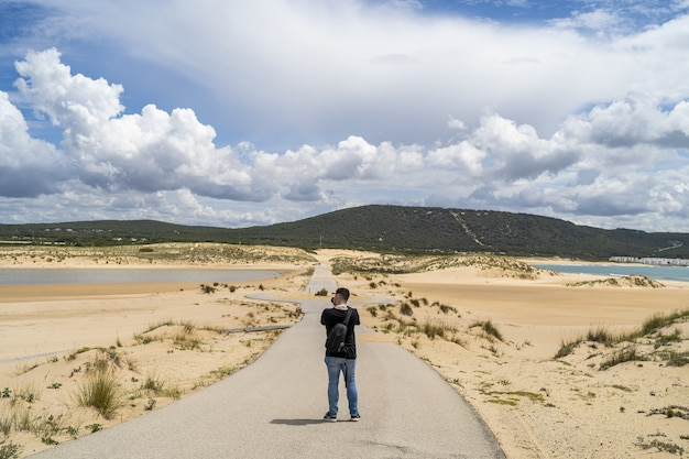 Male photographer walking through a beach under a cloudy sky at daytime in andalusia, spain