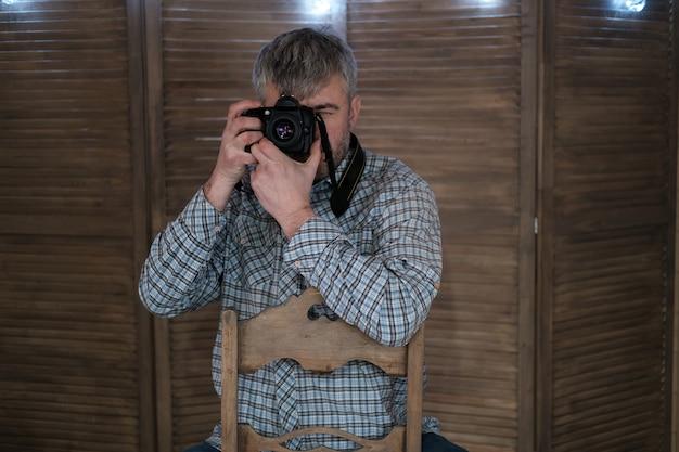 Фотограф-мужчина с фотоаппаратом над деревянной стеной