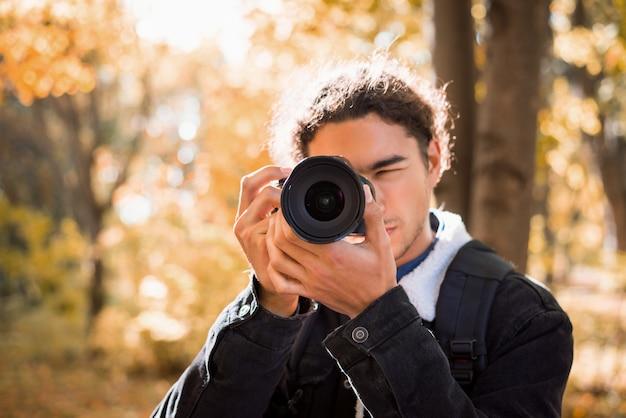 晴れた秋の日に公園の自然の写真を撮るアマチュアカメラを持つ男性カメラマン