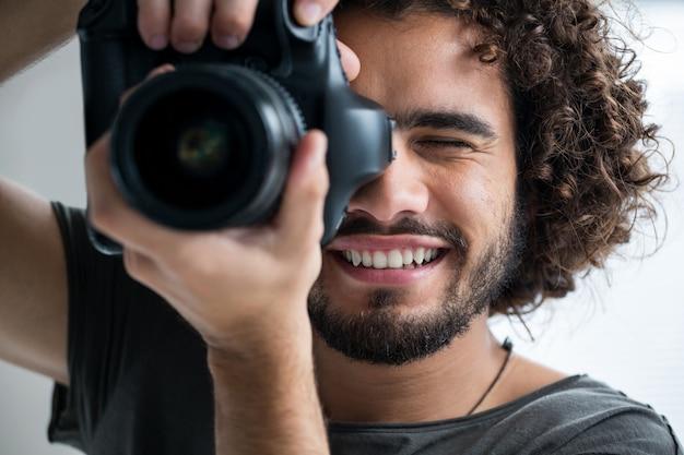 Мужской фотограф с цифровой камерой в студии