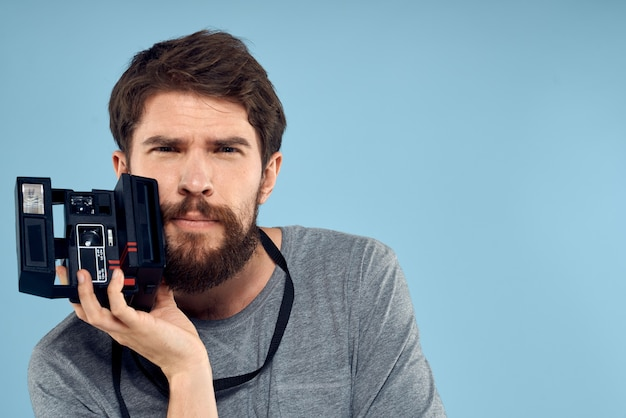 Male photographer with a professional camera in his hands near the face of a hobby creative approach blue background. high quality photo