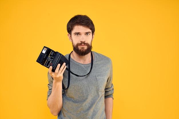 プロの写真カメラを持つ男性の写真家。プロのクリエイティブアプローチスタジオ黄色の背景。高品質の写真