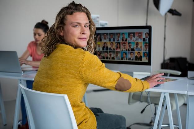 Мужской фотограф работая над компьютером на столе