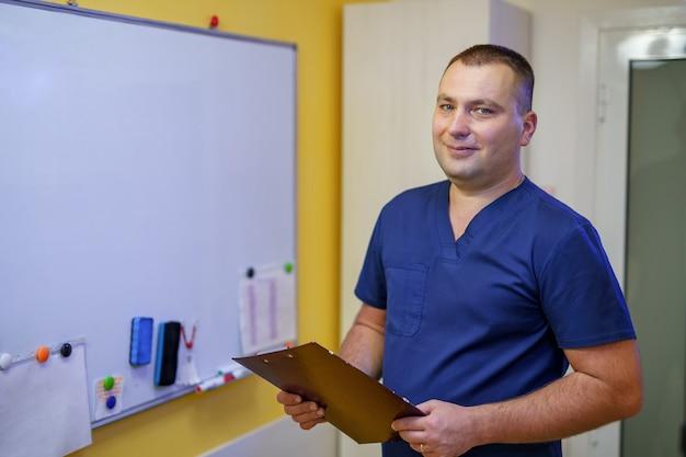 メモ付きのボードの近くにメモ帳を持つ男性医師。健康と病院のコンセプト。